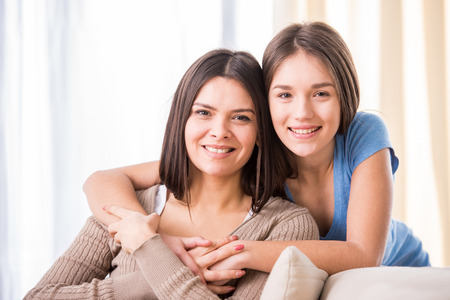 teens: Beautiful mother and her cute daughter smiling and posing at home.