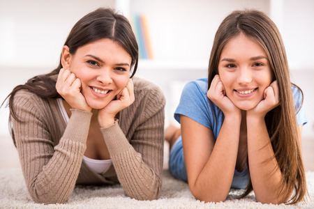 Smiling mother and her teen daughter are lying on the floor and looking at the camera. 版權商用圖片