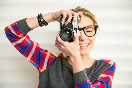 girl with camera: Close-up of trendy girl face in sunglasses with vintage camera.