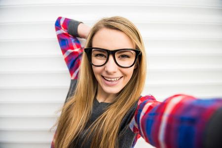 sexy young girl: Крупным планом лицо девушки модный в очках делает selfie фото.