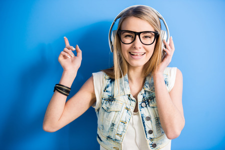 girl with headphones: Trendy, blonde girl is listening a music with headphone on blue background. Stock Photo