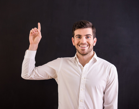 caucasians: Portrait of attractive young man points his finger up, on dark background.