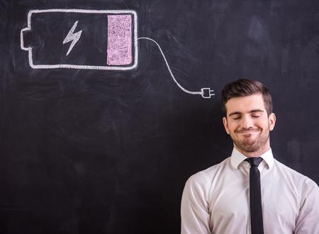 Lachende man staat tegen het bord met het opstellen batterij bijna leeg.