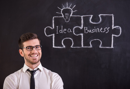 Handsome young man is standing against blackboard with connecting jigsaw pieces. Idea and business concept. photo