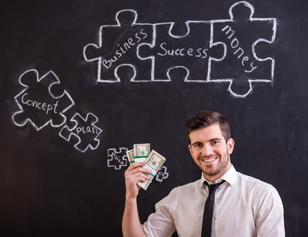 Smiling man is holding money and looking for a new ideas for business. Blackboard with connecting jigsaw pieces. photo