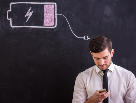buttery: Young man is holding  his smartphone with battery low while standing against the blackboard with drawing buttery low