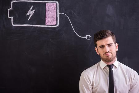 Jonge vermoeide man staat tegen het schoolbord met de tekening van de batterij laag.