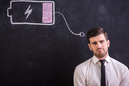 Young tired man is standing against the blackboard with drawing battery low.