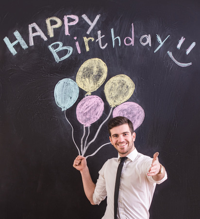 adult birthday: Happy young man is standing against drawing balloon and happy birthday on the blackboard.