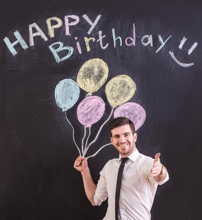 red  man: Hombre joven feliz que est� de pie en contra de sacar el globo y feliz cumplea�os en la pizarra.