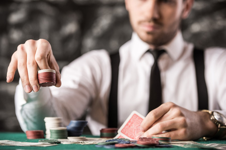 poker: View of young, confident, gangster man in shirt, suspenders and hat, while hes playing poker game.