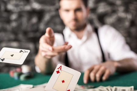 Young, confident, gangster man in shirt and suspenders, is throwing his cards on poker table, while hes playing poker game. Stock Photo
