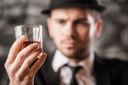 Young, confident, gangster man is drinking a whisky.