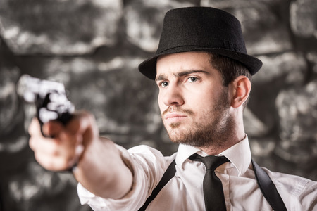 View of a gangster man is holding a gun. photo