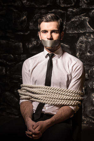 Kidnapped and tied up young man is sitting on the chair in dark room.