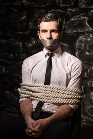 gefesselt: Entf�hrt und gefesselt junger Mann sitzt auf dem Stuhl im dunklen Raum sitzen. Lizenzfreie Bilder