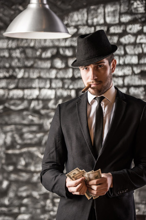 man holding money: View of a gangster man is smoking a cuban cigar and holding money. Stock Photo