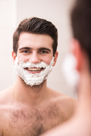 Shaving with fun. Rear view of playful young man with shaving cream on his face is standing in front of the mirror and smiling. photo