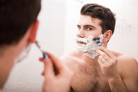male grooming: Handsome young man is shaving his face and looking at the mirror. Stock Photo
