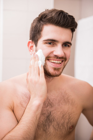 Portrait of a handsome young man is applying shaving cream to his face. photo