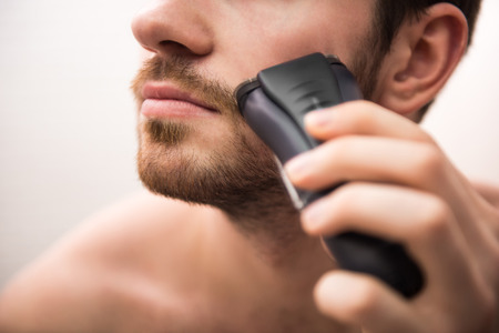 electric razor: Handsome young man is shaving with electric razor while looking at the mirror. Stock Photo
