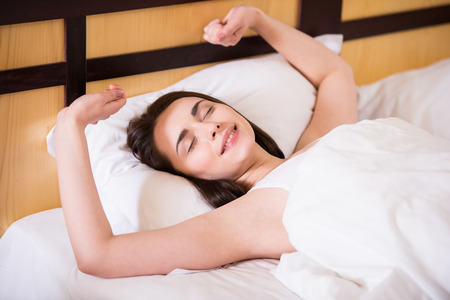Top view of young beautiful, woman is waking up fully rested. Stock Photo
