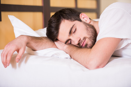 smiling young man: Close-up of young man is sleeping on bed. Stock Photo