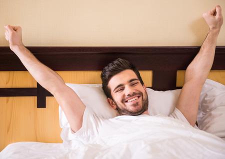 despertarse: Joven, guapo está despertando completamente descansado.