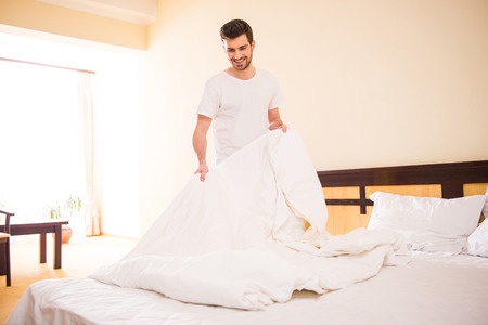 Young male is making bed in hotel room.