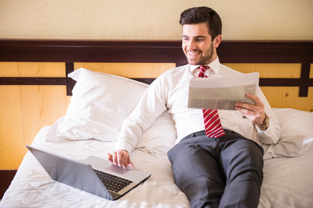 working attire: Handsome businessman is working with laptop, sitting on the bed in hotel room. Stock Photo