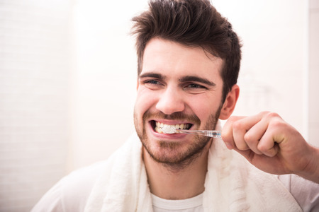 clean teeth: Morning routine of washing the teeth. Handsome young man is brushing teeth with toothbrush.