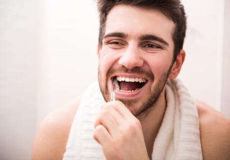 歯を洗浄の朝のルーチン。ハンサムな若い男は歯ブラシと笑顔で歯を磨いています。
