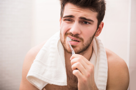 Morning routine of washing the teeth. Handsome young man is brushing teeth with toothbrush.