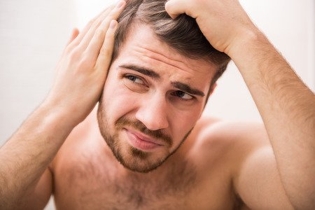 receding: Handsome man is checking hairline while looking at the mirror.