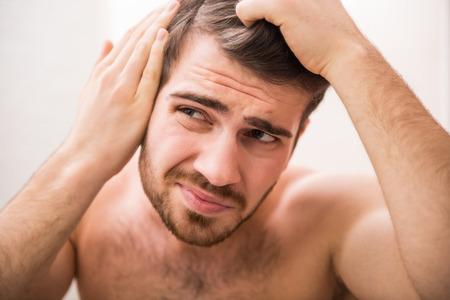 calvicie: Hombre guapo está comprobando la línea del cabello mientras se mira en el espejo. Foto de archivo