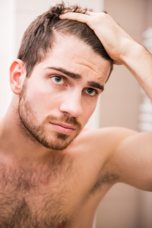 mens: Handsome man is checking hairline while looking at the mirror.