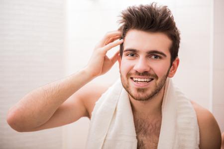 calvicie: Apuesto joven está mirando el espejo y sonríe. Foto de archivo