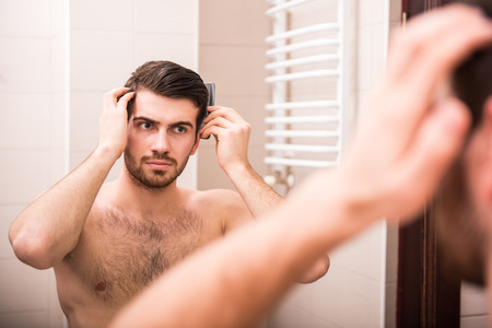 Morning hygiene. Handsome man is combing his hair, looking at the mirror. photo