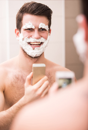 Shaving with fun. Rear view of playful young man with shaving cream on his face is standing in front of the mirror and making selfie. photo