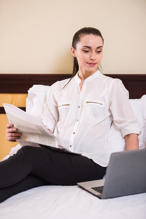 Young business woman is using laptop, sitting in hotel room. photo