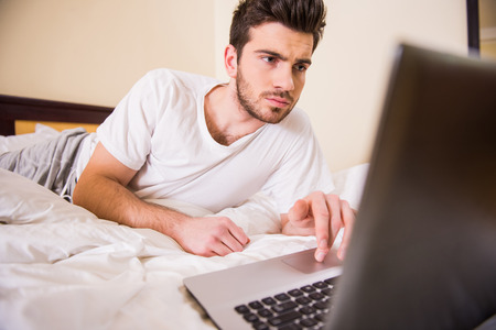 stay home work: Smiling young man is working with laptop, lying on bed.