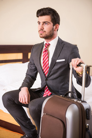 Young businessman is sitting at the hotel room with suitcase. photo