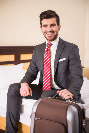 Young businessman is sitting at the hotel room with suitcase and looking at the camera. photo