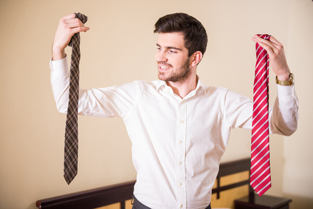 hand job: Young businessman is choosing tie at the hotel room.