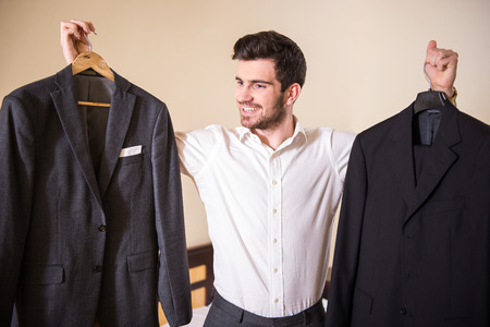 suit man: Choosing a suit for meeting. Businessman is standing with a suit in each hand and choosing the best one to wear.