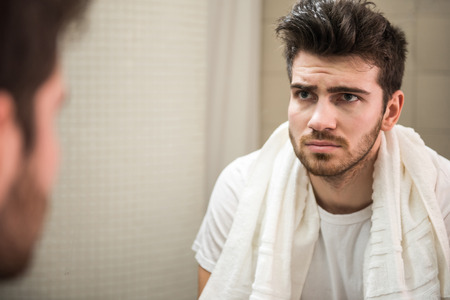 on mirrors: Tired young man is looking at the mirror. Stock Photo
