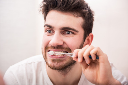 Morning routine of washing the teeth. Handsome young man is brushing teeth with toothbrush. photo