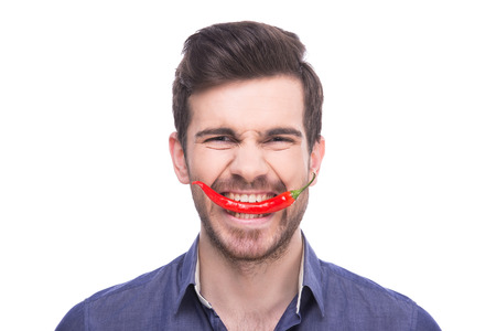 chili: Handsome young man is holding chili pepper in his teeth while standing against white background. Stock Photo