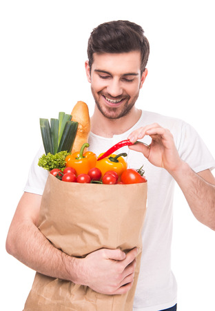 Young man is holding a bag full of vegetables, on white background.