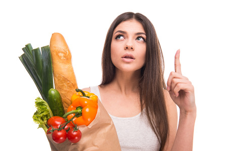 Young woman is holding a bag full of vegetables and thinking about something, on white background. photo